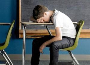 bambino a scuola testa sul banco
